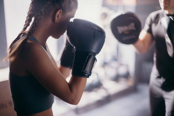Teenage girl doing boxing drills with her coach