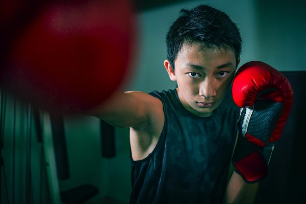 Young teen boy with red boxing gloves
