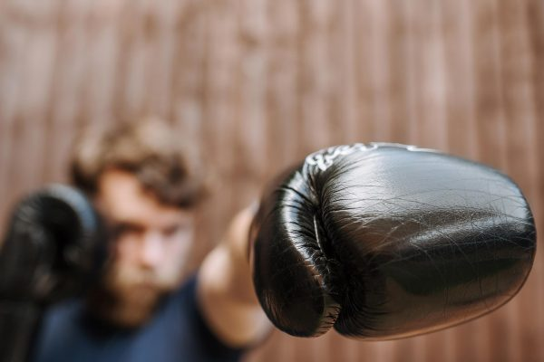 Teen boy with black boxing gloves