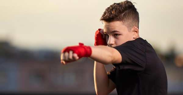 Teen boy with red boxing gloves